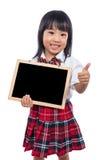 Lavagna cinese asiatica della tenuta della bambina con i pollici su Fotografia Stock Libera da Diritti