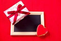 Lavagna con il biscotto sotto forma della scatola di regalo e del cuore su un fondo rosso fotografie stock libere da diritti