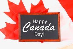 Lavagna con il giorno felice del Canada di parola sulla bandiera nazionale Festività del 1° luglio Immagine Stock
