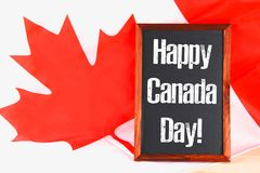Lavagna con il giorno felice del Canada di parola sulla bandiera nazionale Festività del 1° luglio Fotografie Stock Libere da Diritti