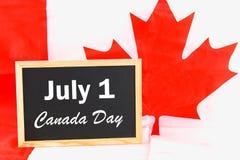 Lavagna con il giorno felice del Canada di parola sulla bandiera nazionale Festività del 1° luglio Fotografia Stock