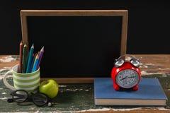 Lavagna con il libro, il supporto della penna, la mela e gli occhiali Fotografia Stock