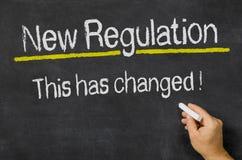 Lavagna con il nuovo regolamento del testo Immagini Stock Libere da Diritti