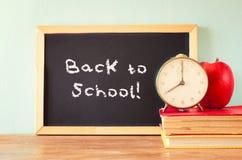 Lavagna con la frase di nuovo alla scuola, all'orologio della mela ed alla pila di libri Immagine filtrata Immagine Stock Libera da Diritti