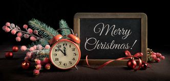 Lavagna con la sveglia e decorazioni di Natale sul nero Fotografia Stock Libera da Diritti