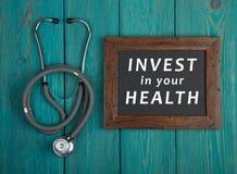 Lavagna con testo & x22; Investa nel vostro health& x22; e stetoscopio su fondo di legno blu Fotografie Stock Libere da Diritti