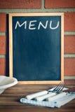 Lavagna del menu prima del muro di mattoni Immagine Stock