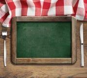 Lavagna del menu sulla tabella con la lama e la forcella Immagine Stock