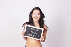 Lavagna della tenuta della giovane donna che dice allenamento del corpo della spiaggia Immagini Stock