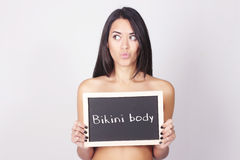 Lavagna della tenuta della giovane donna che dice il corpo del bikini Fotografie Stock Libere da Diritti