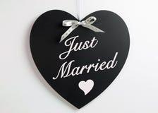Lavagna di forma del cuore con il nastro bianco dei cuori contro un fondo bianco con appena il messaggio sposato Immagini Stock Libere da Diritti