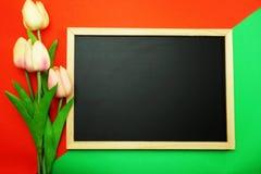 Lavagna e mazzo di fiore della peonia sulla disposizione piana del fondo rosso e verde fotografia stock libera da diritti