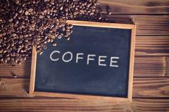 Lavagna nera con i chicchi di caffè Immagine Stock
