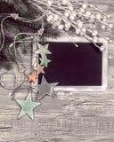 Lavagna nera con le decorazioni di inverno, spazio del testo Immagine Stock Libera da Diritti