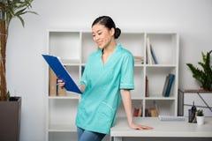 Lavagna per appunti asiatica della tenuta dell'internista con la diagnosi e la condizione nella clinica immagini stock