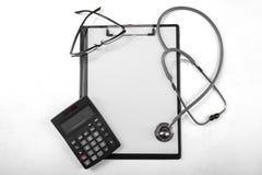 Lavagna per appunti con il calcolatore e lo stetoscopio Immagini Stock