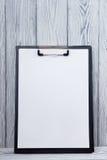 Lavagna per appunti con il foglio bianco di carta su fondo di legno Copi lo spazio Immagini Stock Libere da Diritti
