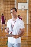Lavagna per appunti della tenuta dell'allenatore di pallacanestro nella corte Immagine Stock Libera da Diritti