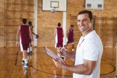 Lavagna per appunti della tenuta dell'allenatore di pallacanestro nella corte Immagini Stock Libere da Diritti