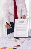 Lavagna per appunti della tenuta dell'uomo d'affari con la lista di controllo contro Fotografie Stock