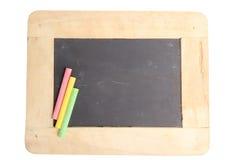 Lavagna per lo spazio della copia con i pezzi di gesso variopinti su fondo bianco Fotografia Stock