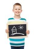 Lavagna sorridente della tenuta del ragazzino con la casa Fotografie Stock Libere da Diritti