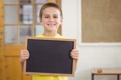 Lavagna sorridente della tenuta dell'allievo in un'aula Fotografie Stock