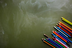 Lavagna verde e un insieme delle matite colorate Fotografia Stock