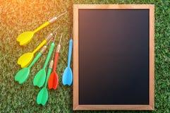 Lavagna vuota con la freccia variopinta del dardo sul pavimento dell'erba jpg immagini stock libere da diritti