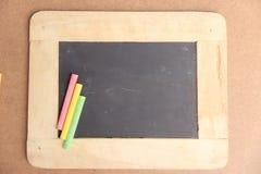 Lavagna vuota per lo spazio della copia con i pezzi di gesso variopinti Fotografia Stock Libera da Diritti