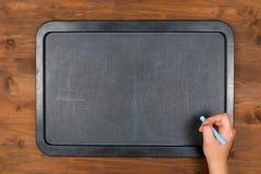 Lavagna vuota sulla tavola di legno con la mano con gesso Immagine Stock Libera da Diritti