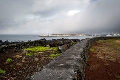 Lavaküstenlinie mit einer Lavawand am Hafen auf der Insel von Pico Lizenzfreies Stockfoto