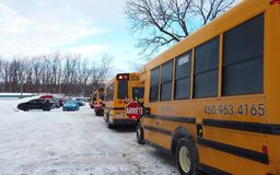 Laval, Quebec, CANADA – February 14, 2019: Laval School Bus`s parked up during the snow in the school or kinder garden parking. Yellow school bus royalty free stock photo
