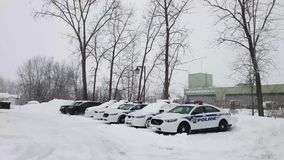 Patrol police cars parked in the parking area during snow storm. Laval, Quebec, Canada - February 13, 2019. Patrol police cars parked in the parking area during stock video
