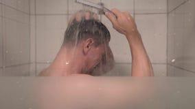 Lavan al hombre joven en la ducha almacen de metraje de vídeo