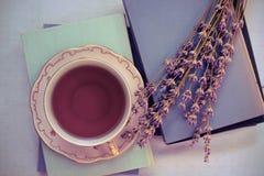 Lavanda y una taza de té en los libros Fotos de archivo libres de regalías