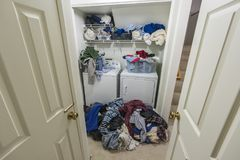 Lavandaria desarrumado com as pilhas da roupa imagens de stock