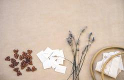 Lavande, boutons en bois, enveloppes faites maison, vieux cercle en bois et rubans avec le bord sur le papier de métier photos stock