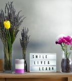 Flowers and home decorations set up with inspirational message 7. Lavander and colorful flowers in vase filled with coffee, candle and smile live and learn royalty free stock photo