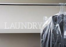 Lavanderia automatica di lavaggio a secco con le camice degli uomini sul gancio immagini stock