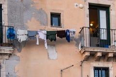 Lavanderia che appende per asciugarsi su un cavo davanti ad una parete molto guastata Fotografia Stock