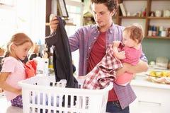 Lavanderia di And Children Sorting del padre in cucina fotografia stock libera da diritti