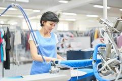 A lavanderia do trabalhador passada veste o ferro seco Foto de Stock