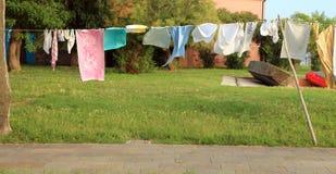 A lavanderia espalhou para fora para secar em uma jarda fotografia de stock