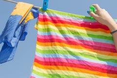 A lavanderia limpa é pendurada acima por uma mulher para secar fotos de stock