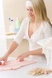 Lavanderia - roupa de dobramento da mulher Foto de Stock