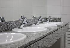 Lavandini e rubinetti multipli alla toilette pubblica Fotografie Stock Libere da Diritti