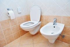 Lavandino della toilette o bidet e carta sanitari della ciotola fotografia stock