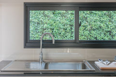 Lavandino di cucina con il rubinetto sul contatore nero Immagine Stock