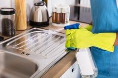 Lavandino di cucina di pulizia di Person Using Spray Bottle For fotografia stock libera da diritti